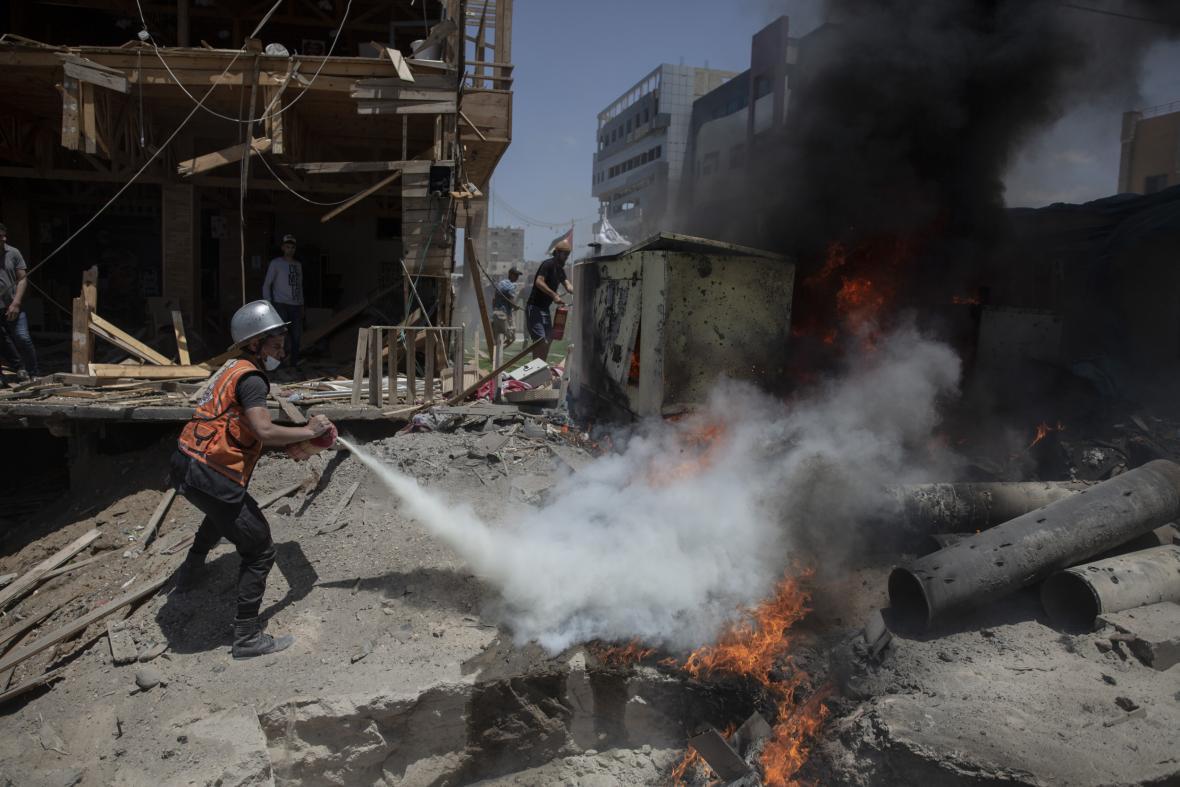 Palestinský hasič hasí oheň z kavárny na pláži v Gaze, kterou zasáhl nálet
