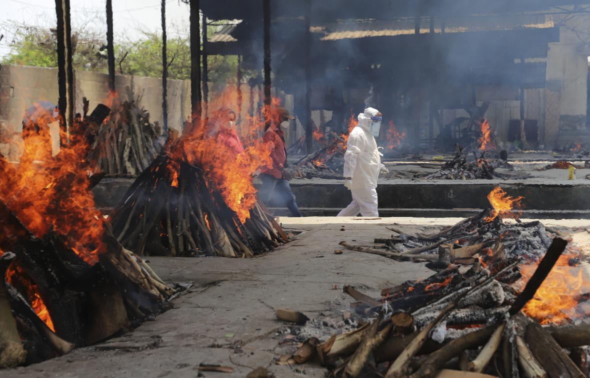 Pracovníci indických úřadů zapalují pohřební ohně s nakaženými