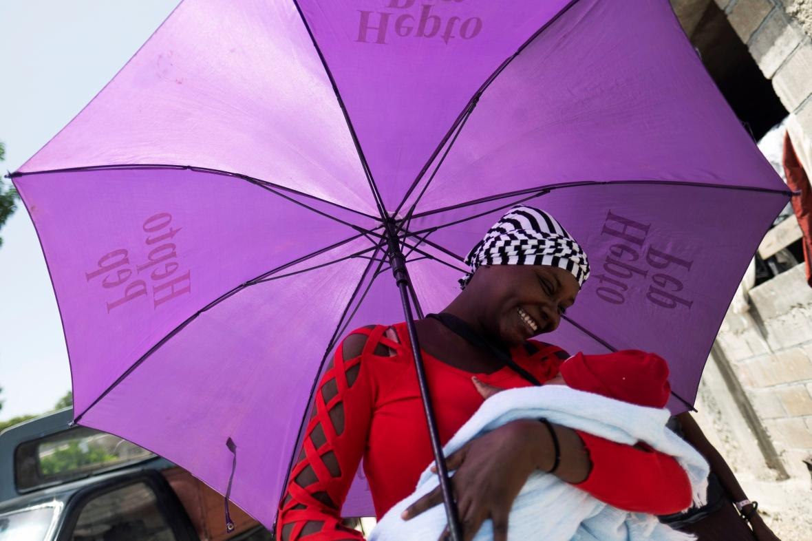 Žena s novorozenětem v domově pro rodiny ohrožené gangy v haitském hlavním městě