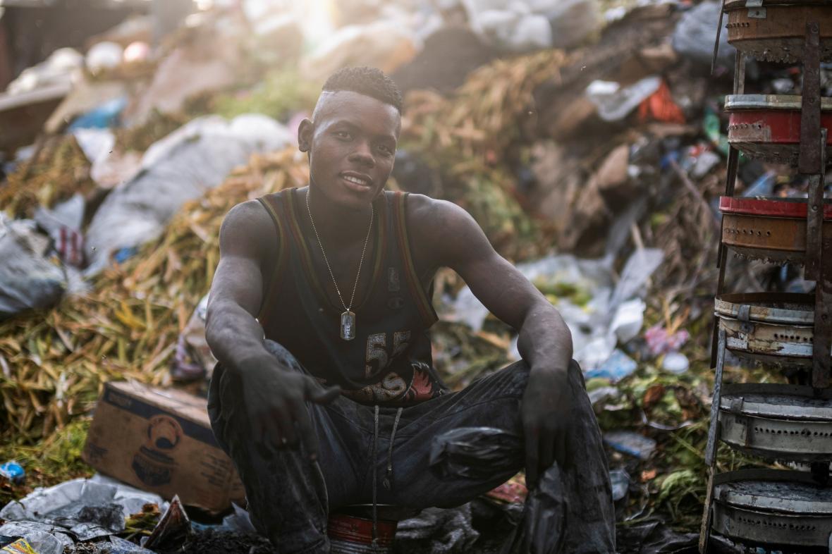 Mladík prodává na ulici v Port-au-Prince dřevěné uhlí