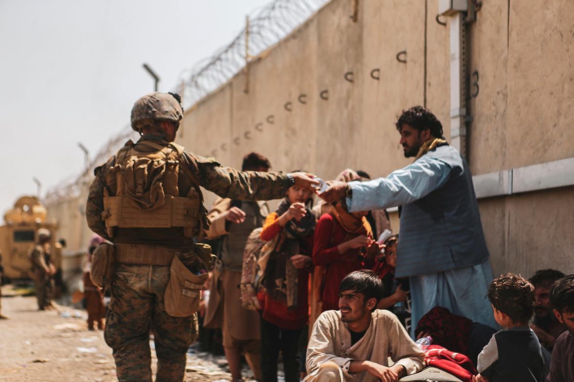 Americký voják roznáší vodu Afgháncům čekajícím na kábulském letišti