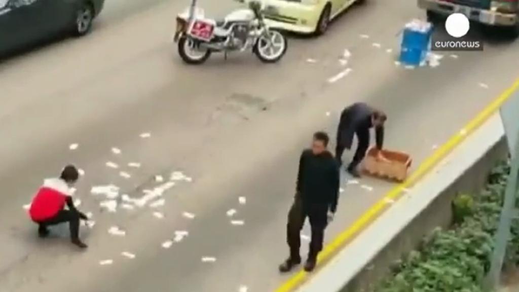 Lidé v hongkongské čtvrti Wan Chai sbírají rozsypané bankovky