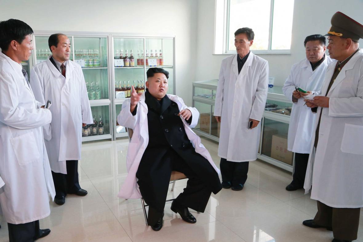 Sedící Kim Čong-un kouká na stojící spoluobčany