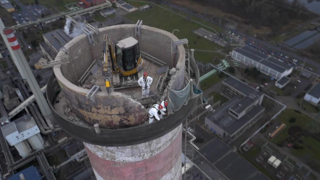 Bagr postupně bourá komín mělnické elektrárny