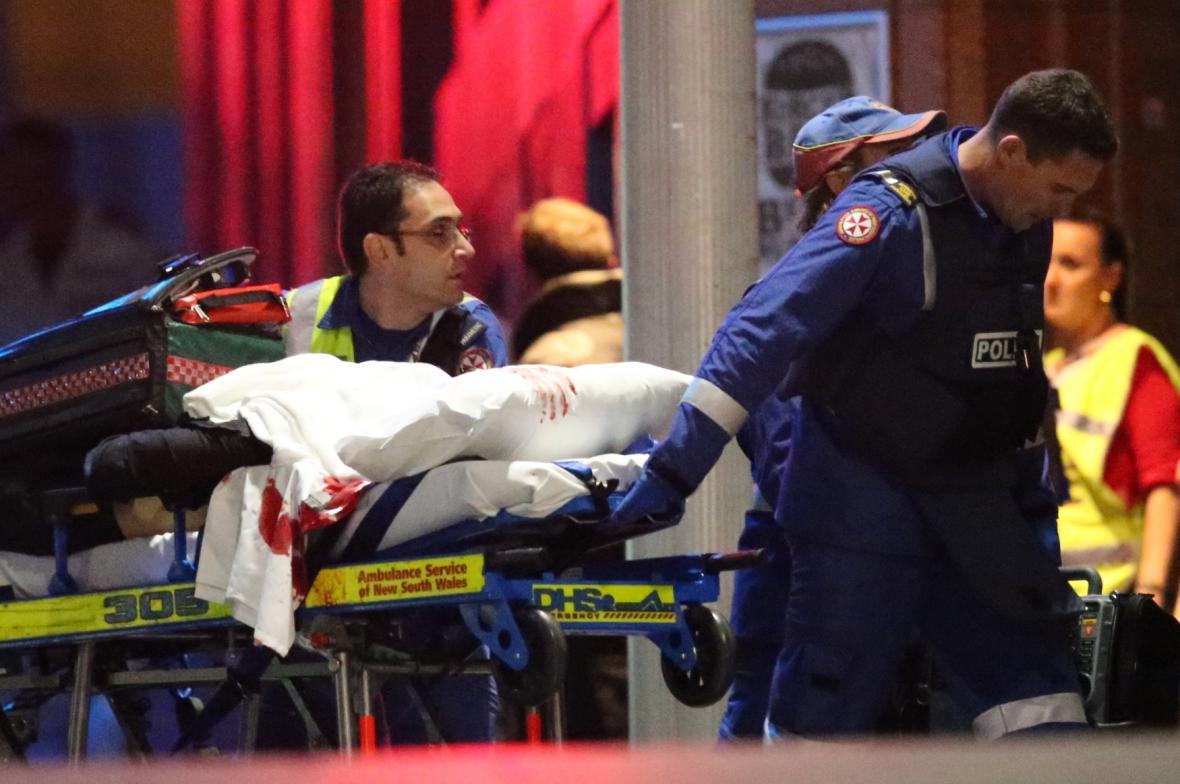 Záchranáři odvážejí zraněné po zásahu v kavárně v Sydney