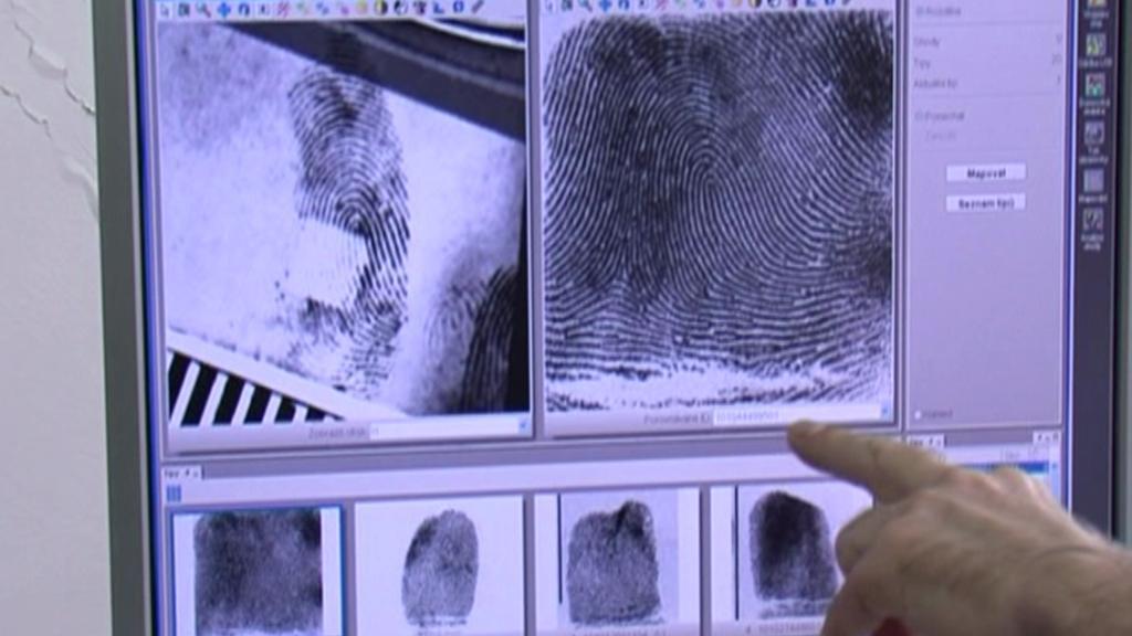 Kriminalista zkoumá otisky prstů