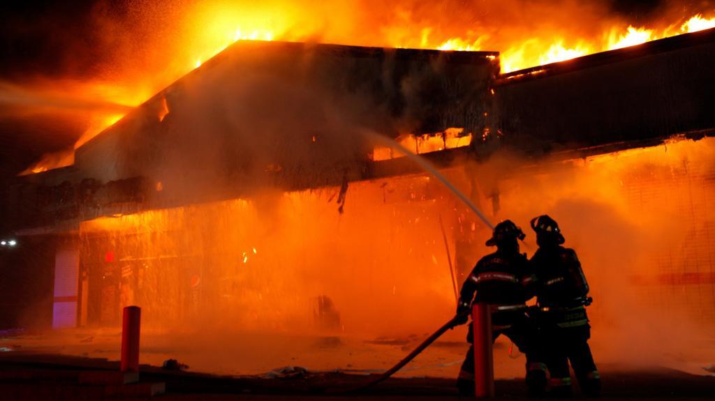 Hašení jednoho ze zapálených domů ve Fergusonu