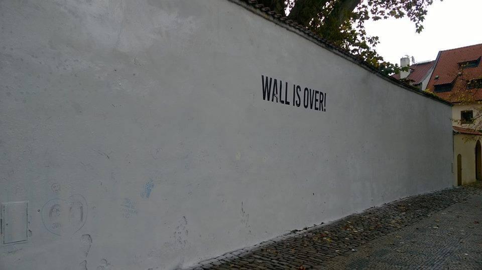 Lennonova zeď přetřená na bílo s nápisem Wall Is Over