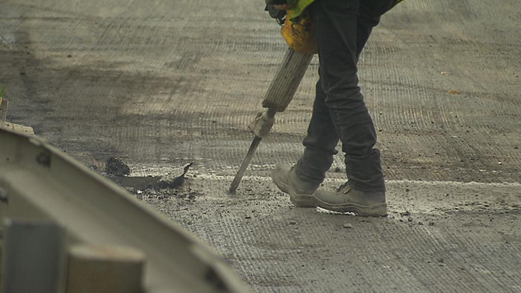 Dělník opravuje vozovku na Jižní spojce
