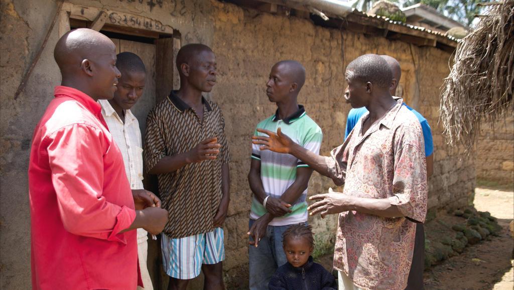 Starosta vesnice (třetí zleva) v diskuzi s místními