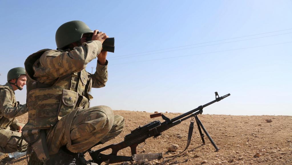 Kurdští vojáci sledují bojovou frontu