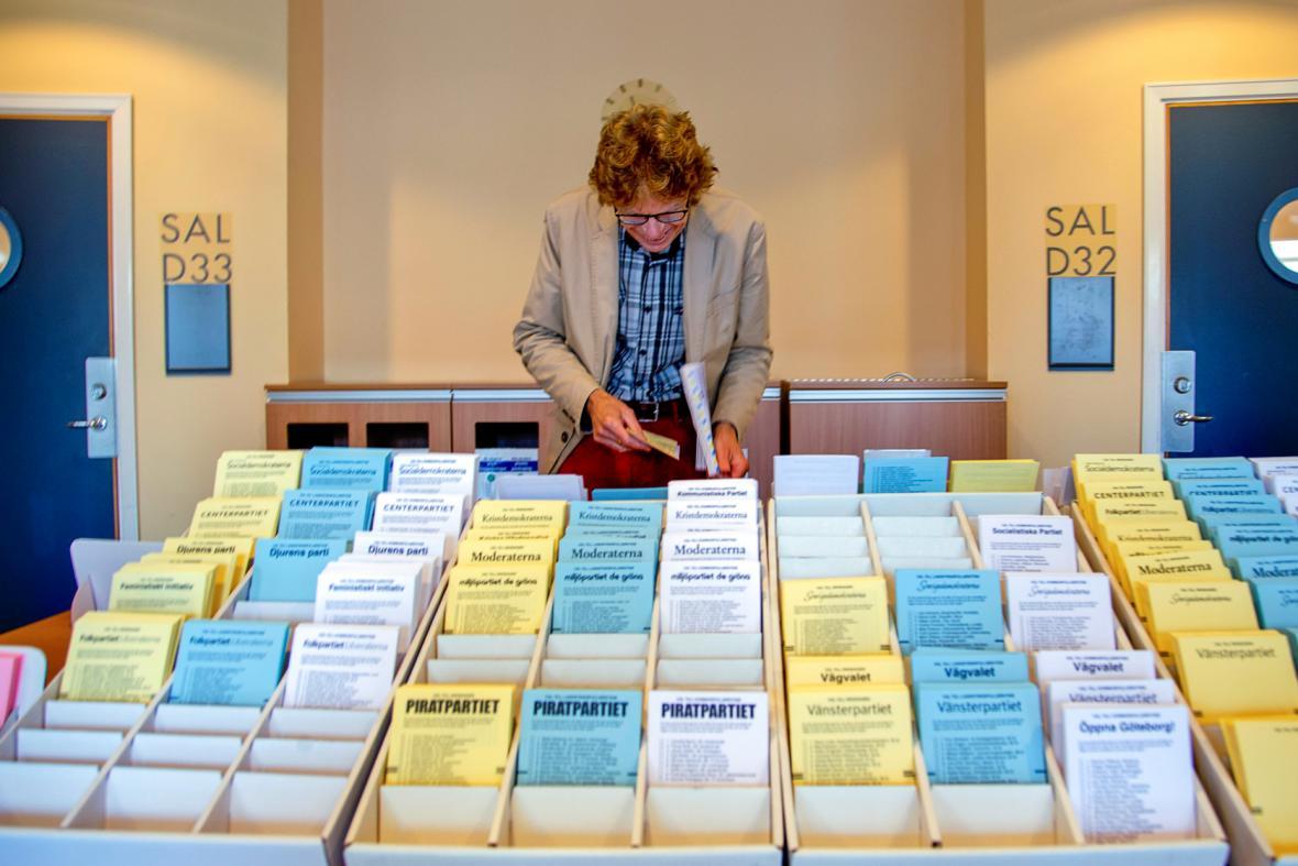 Muž ve volební místnosti v Göteborgu si vybírá z kandidátek