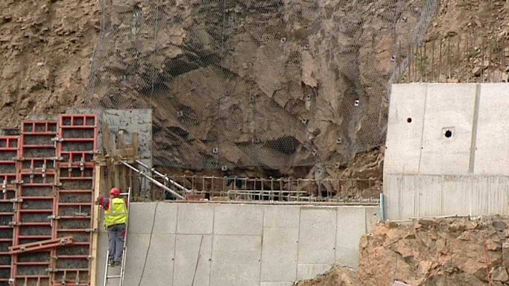 Vchod do štoly mizí za opěrnou zdí