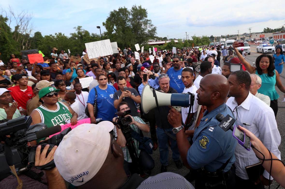 Ron Johnson promlouvá k davu demonstrantů