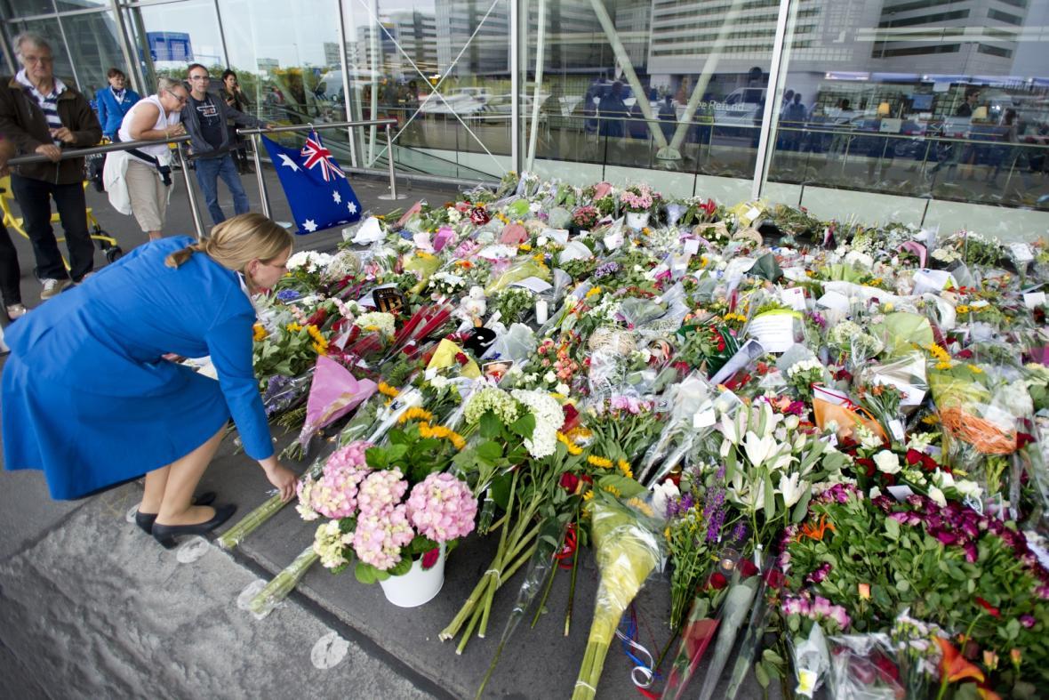 Lidé pokládají květiny před amsterdamské letiště Schiphol