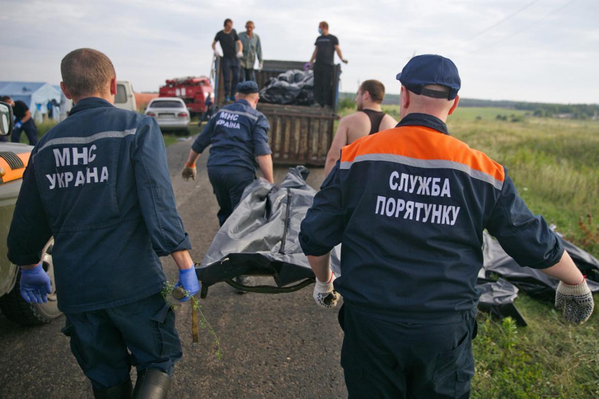 Ukrajinští záchranáři odnášejí těla obětí z havarovaného letounu