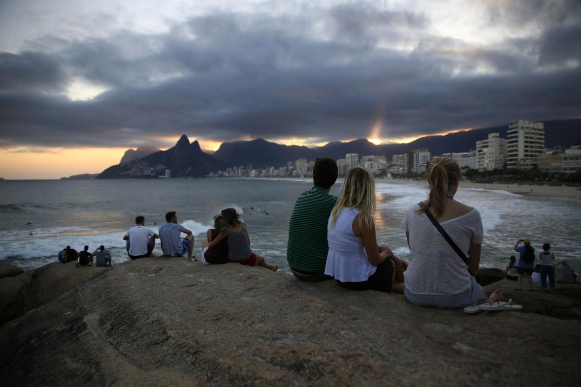 Turisté sledují západ slunce na pláži Copacabana
