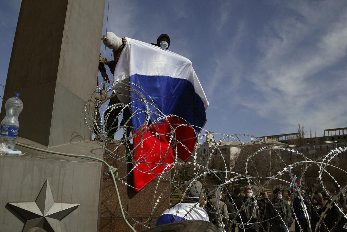 Maskovaný muž držící ruskou vlajku v Doněcku