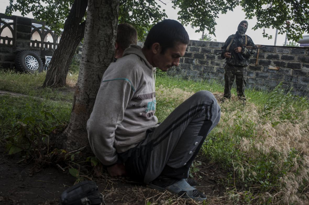 Proruský povstalec hlídá muže podezřelého z rabování ve Slavjansku