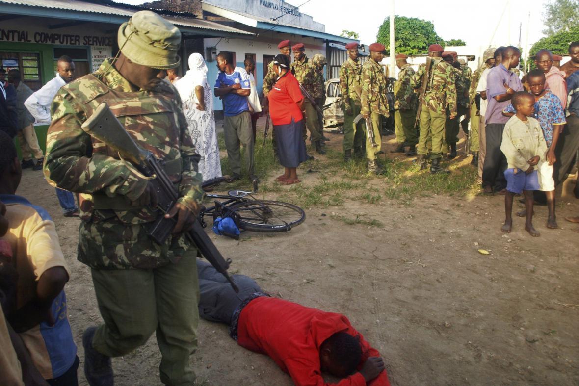 Člen keňských bezpečnotních složek míjí jednu z obětí útoku v Mpeketoni
