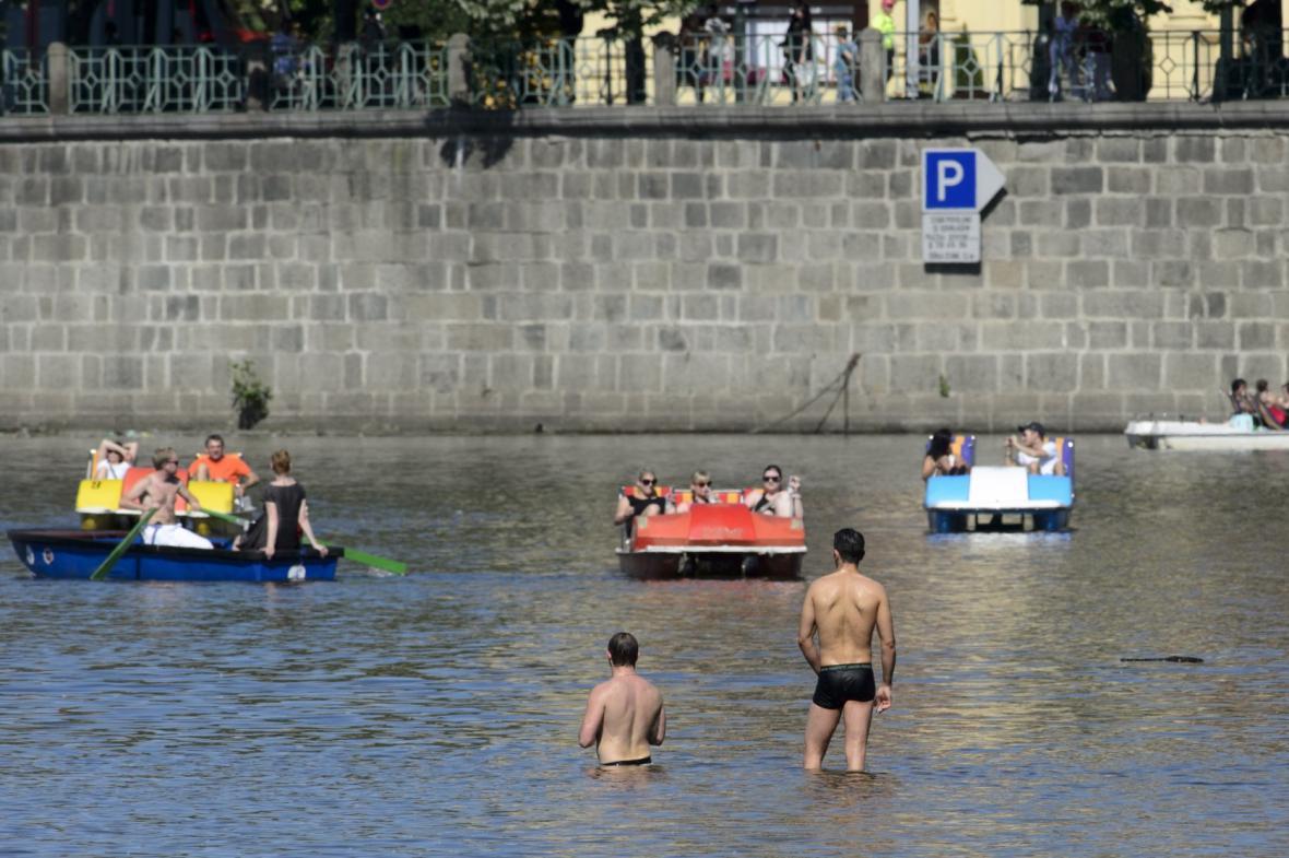 Dvojice mužů se ochlazuje ve Vltavě v centru Prahy