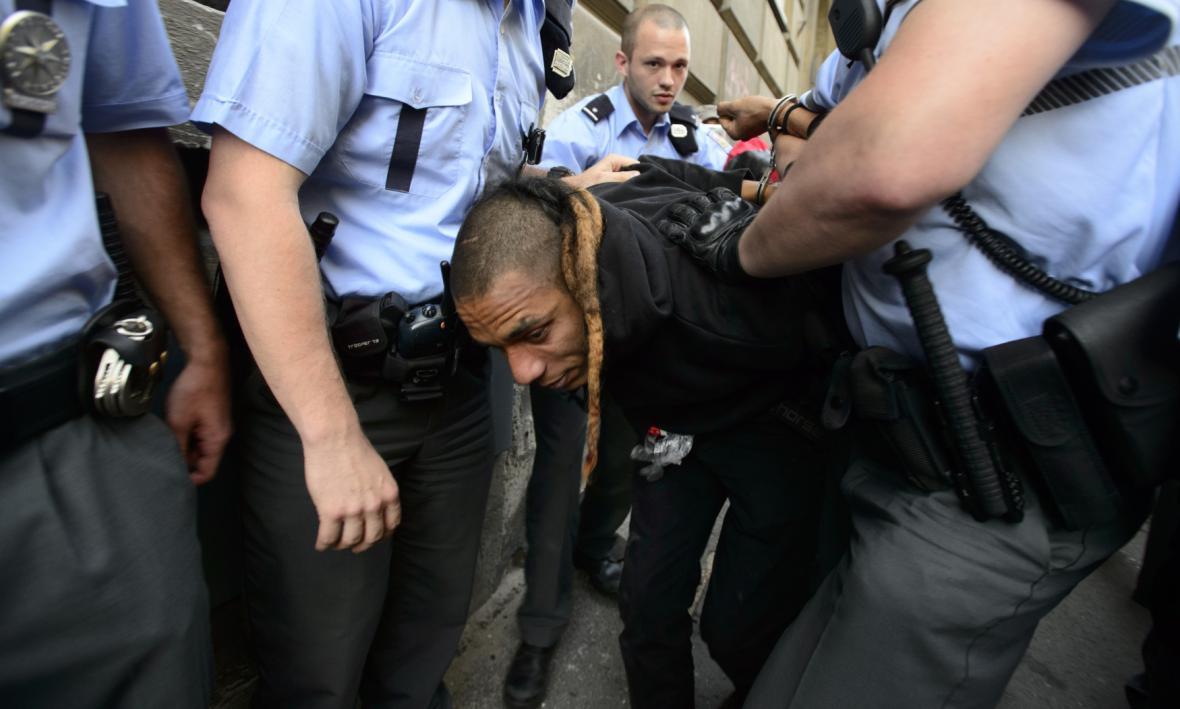 Policisté odvádějí jednoho z účastníků happeningu squatterské iniciativy Obsaď a žij