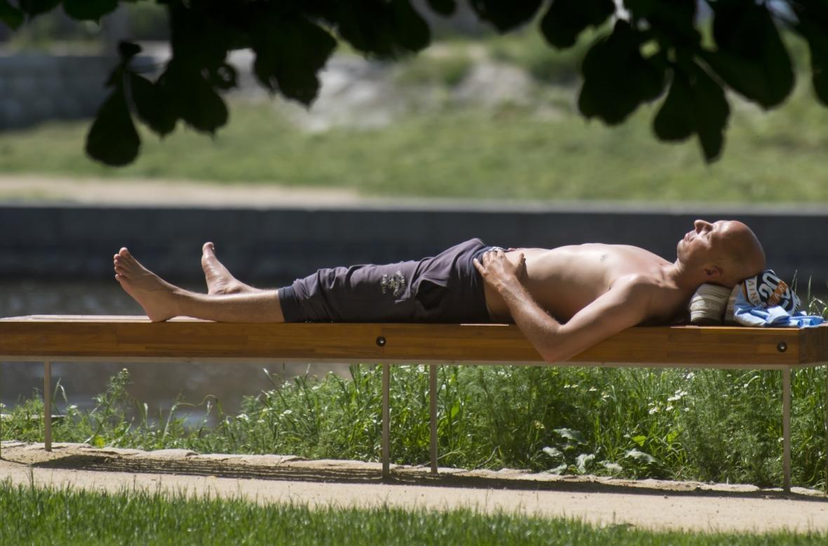 Muž se opaluje na Střeleckém ostrově v centru Prahy