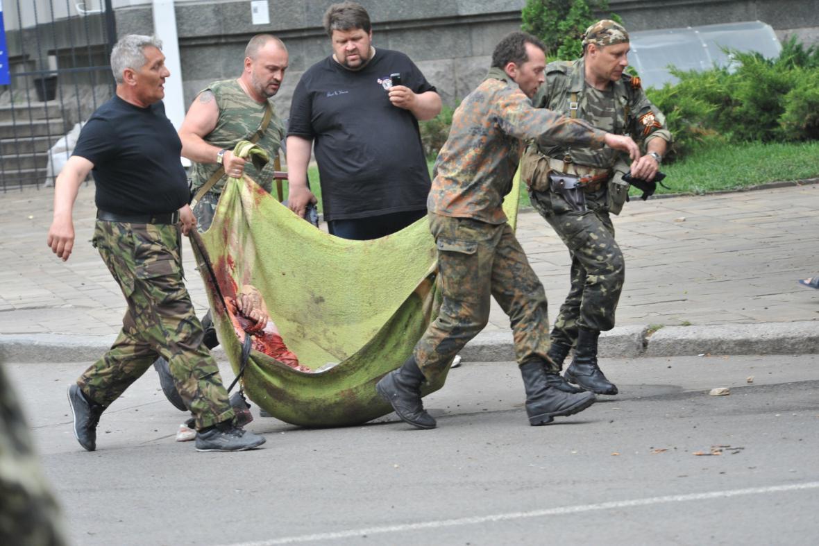 Povstalci odnášejí ze svého poškozeného štábu oběti