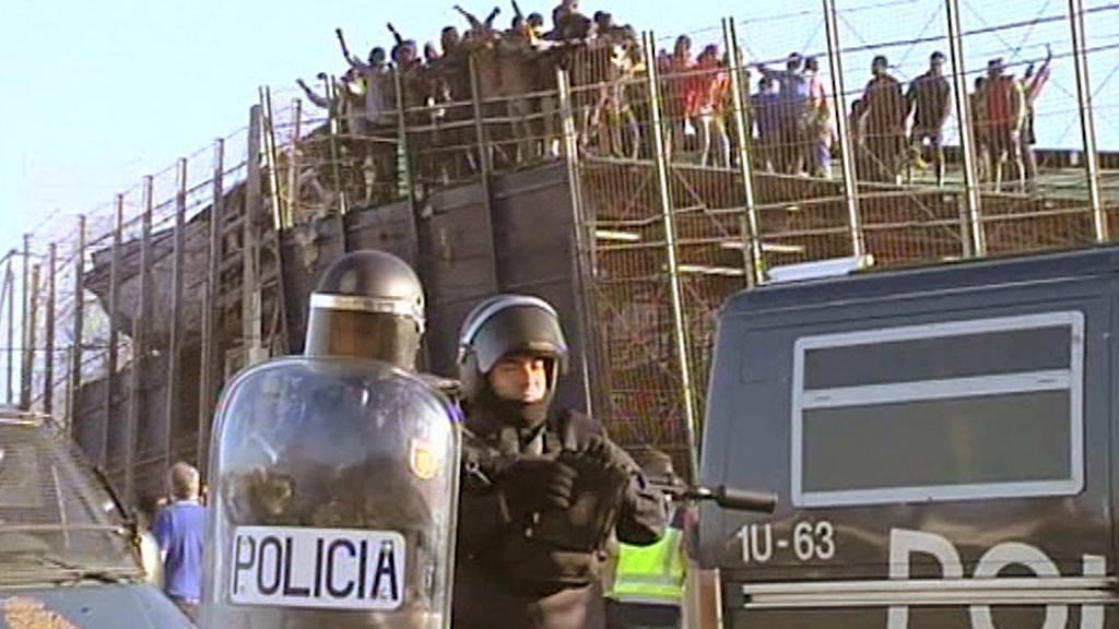 Afričtí imigranti u bariéry v Melille