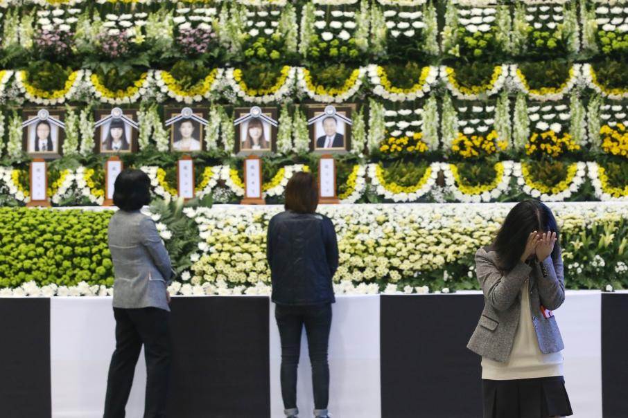 Lidé truchlí u fotografií obětí jihokorejské tragédie