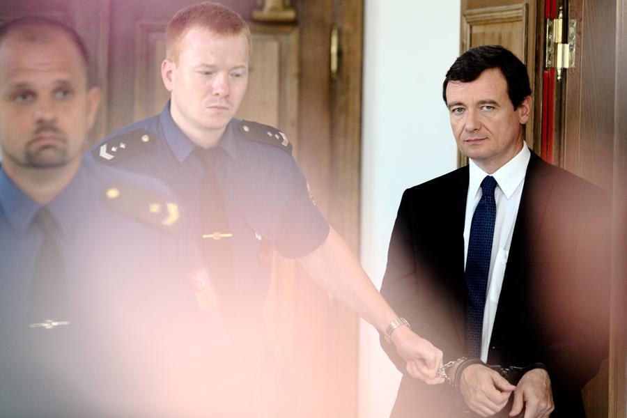Eskorta během přestávky odvádí Davida Ratha ze soudní síně