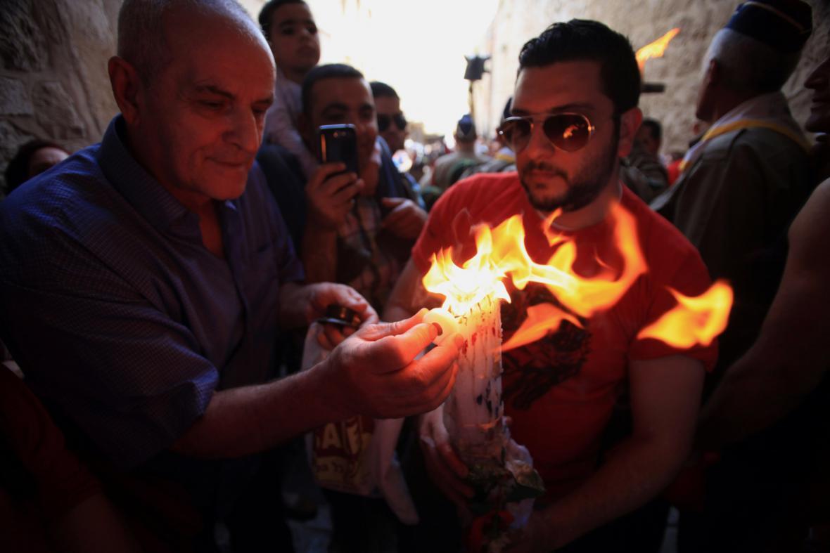 Věřící drží svíčky v Chrámu Božího hrobu