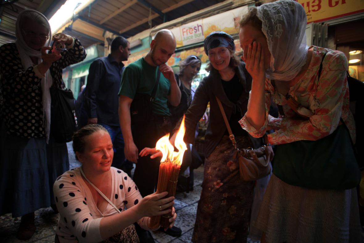 Křesťanští poutníci drží svíčky v Chrámu Božího hrobu