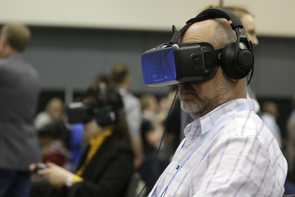 Muž si zkouší brýle pro virtuální realitu Oculus