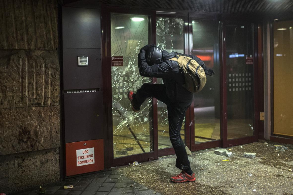 Demonstrant rozbíjí vstupní dveře banky