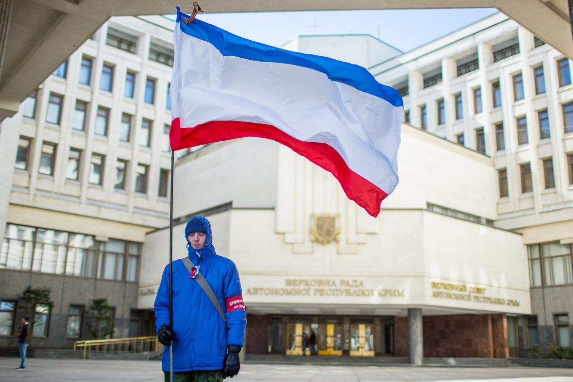 Muž s krymskou vlajkou před budovou krymského parlamentu
