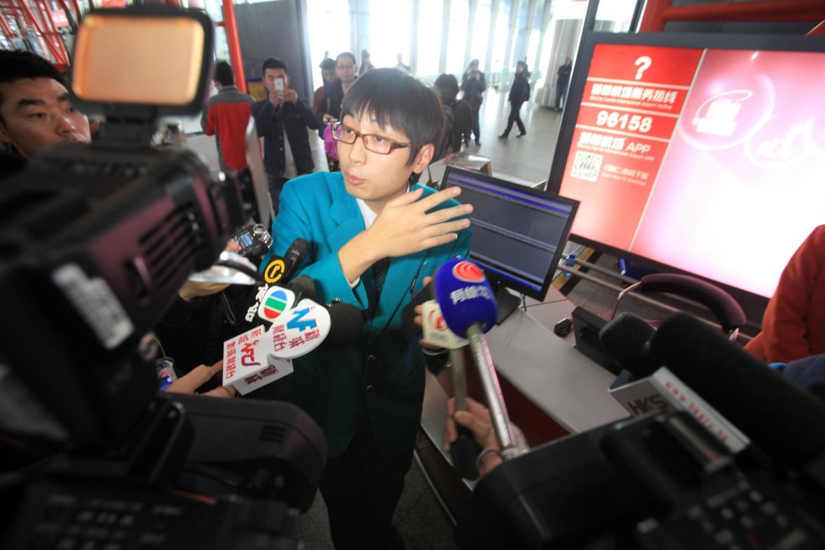 Zaměstnanec společnosti Malaysia Airlines odpovídá na dotazy novinářů