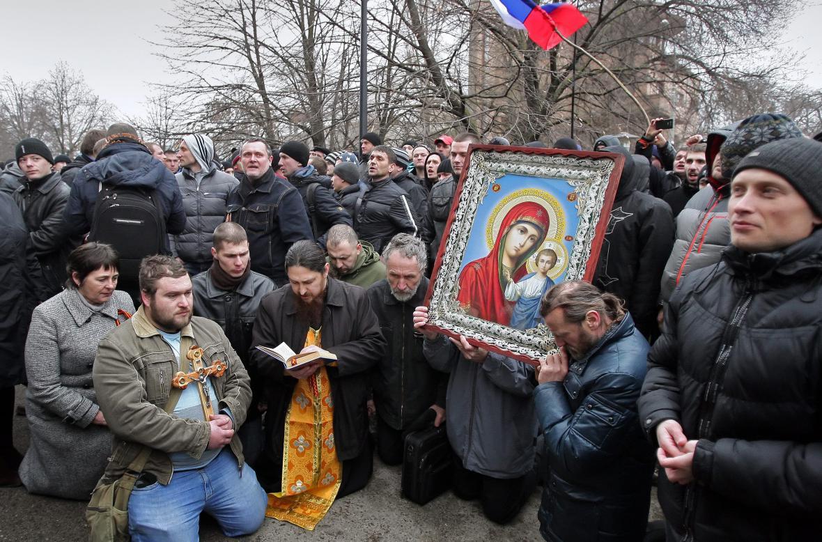 Krymští Rusové a proruští aktivisté se modlí poblíž budovy krymského parlamentu