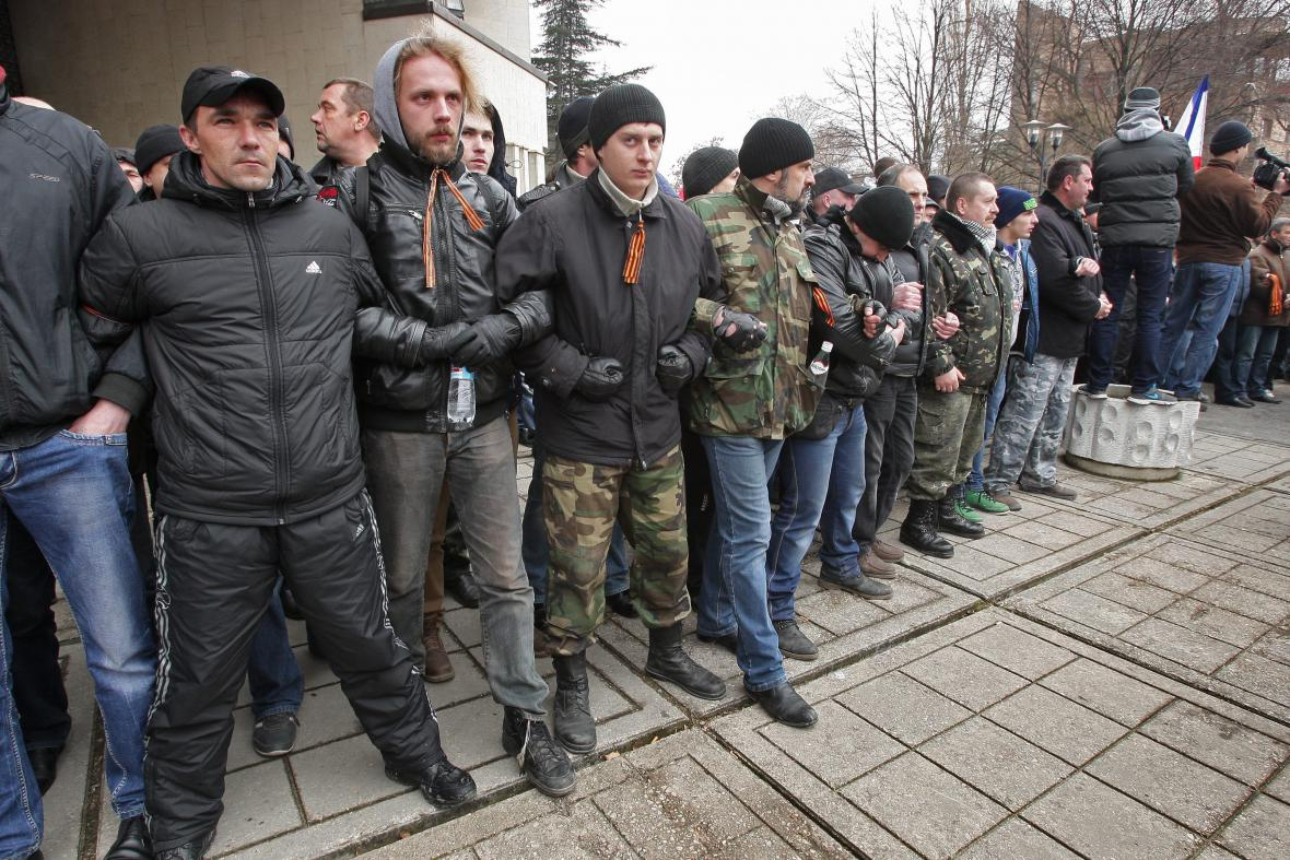 Proruští demonstranti se sepjatými pažemi stojí proti davu krymských Tatarů