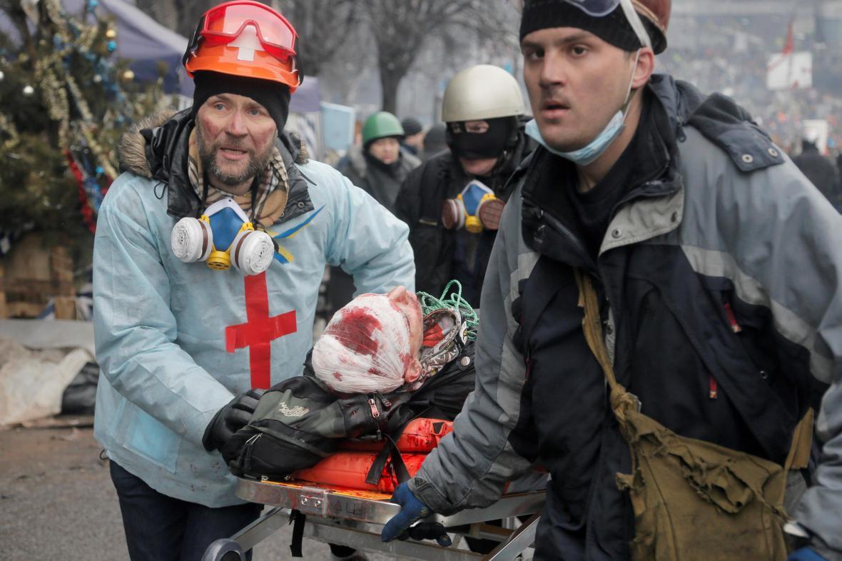 Aktivisté odvážejí zraněného demonstranta