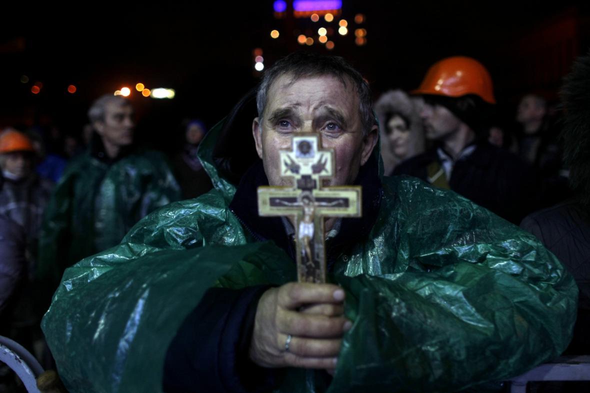 Demonstrant s krucifixem na náměstí Nezávislosti