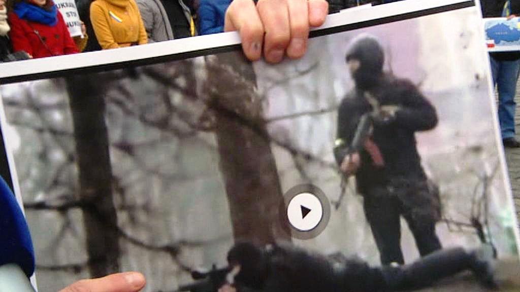 Demonstrant drží obrázek ukrajinských ostřelovačů