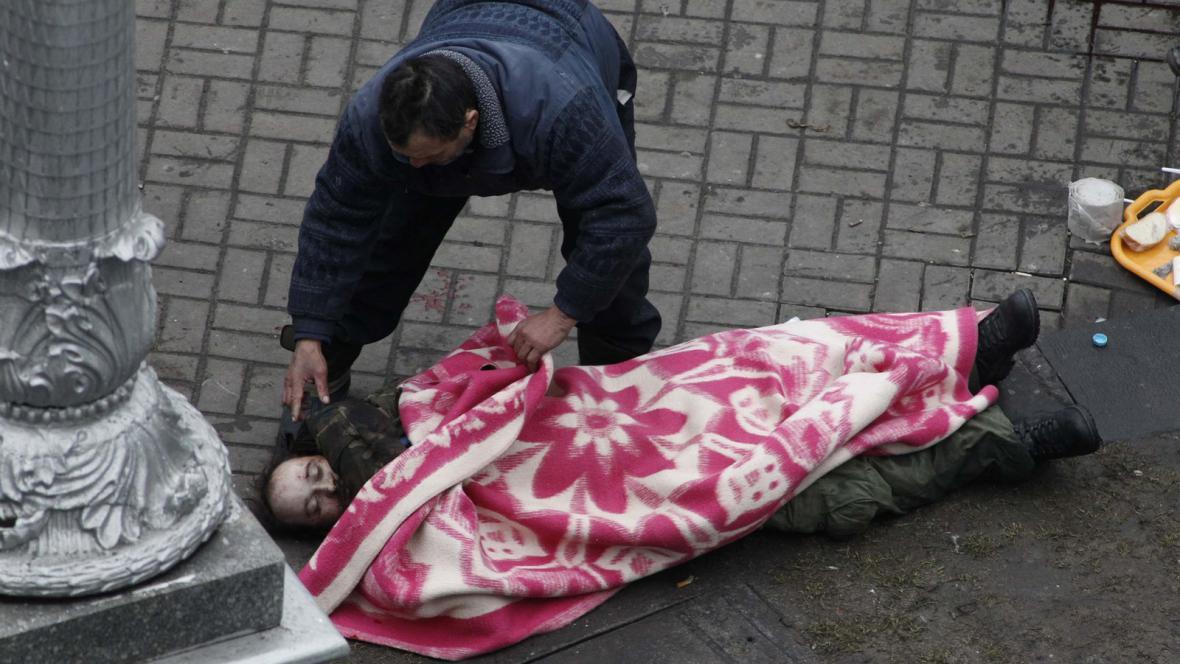 Demonstranti překrývají jednu z obětí pouličních bojů