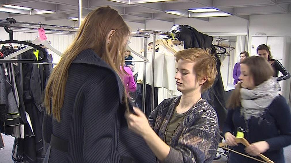 Modelkám pomáhají s oblékáním garderobiéři