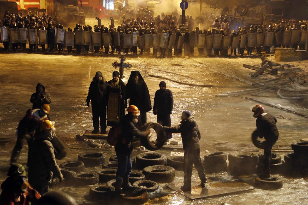 Demonstranti odstraňují z ulic Kyjeva pneumatiky před modlitbou pravoslavných kněží