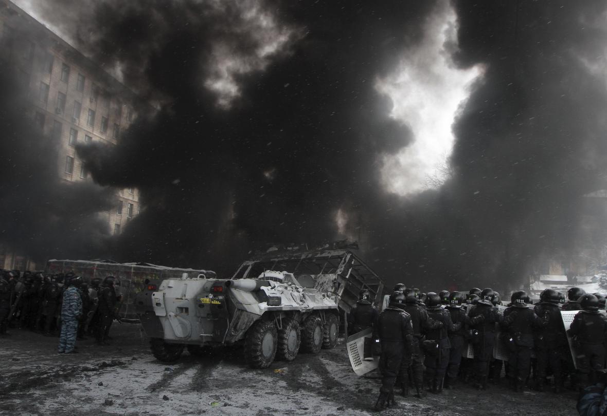 Policejní kordony a těžká technika před hořícími barikádami