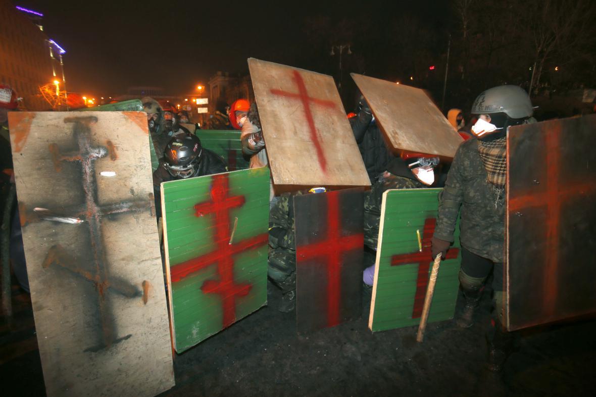 Protestující se chrání před těžkooděnci provizorními štíty