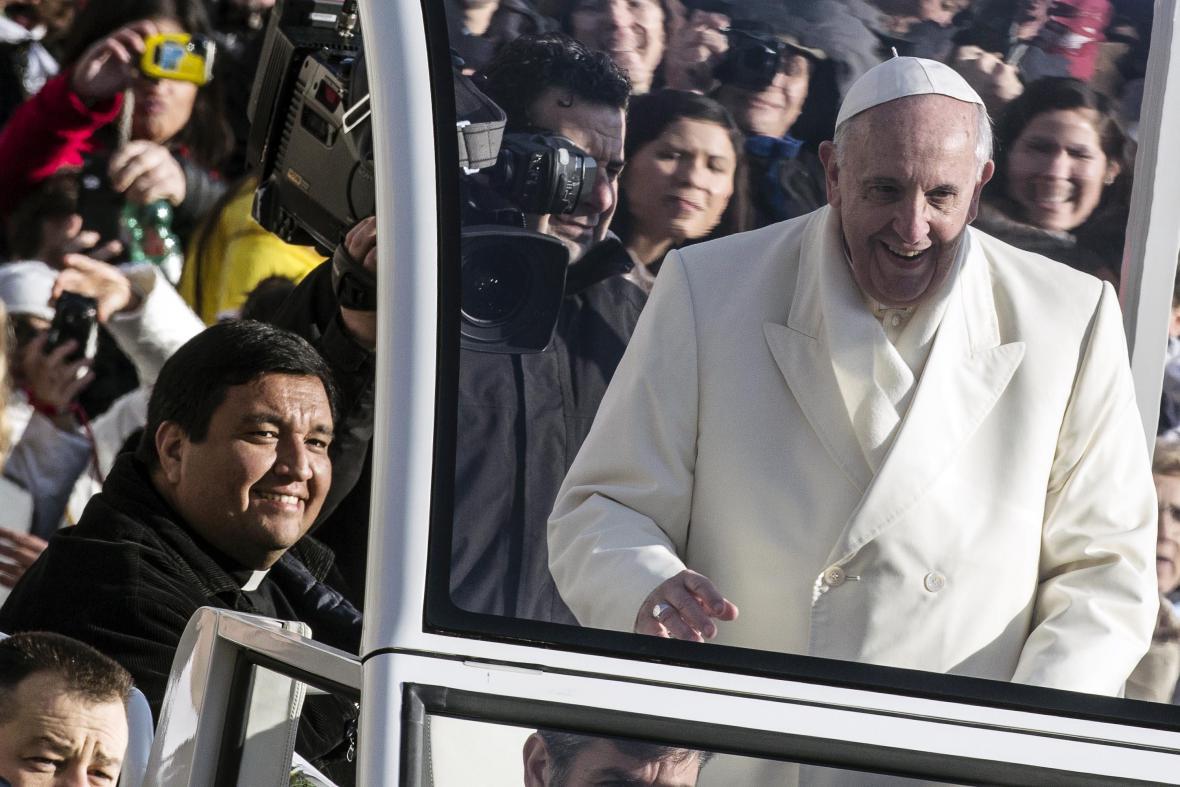 Papež František a kněz Fabien Baez (vlevo) jedou papamobilem