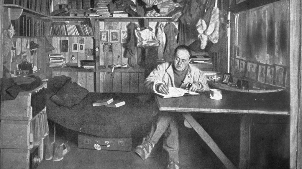 Scott při psaní deníku v chatce poblíž Evansova mysu