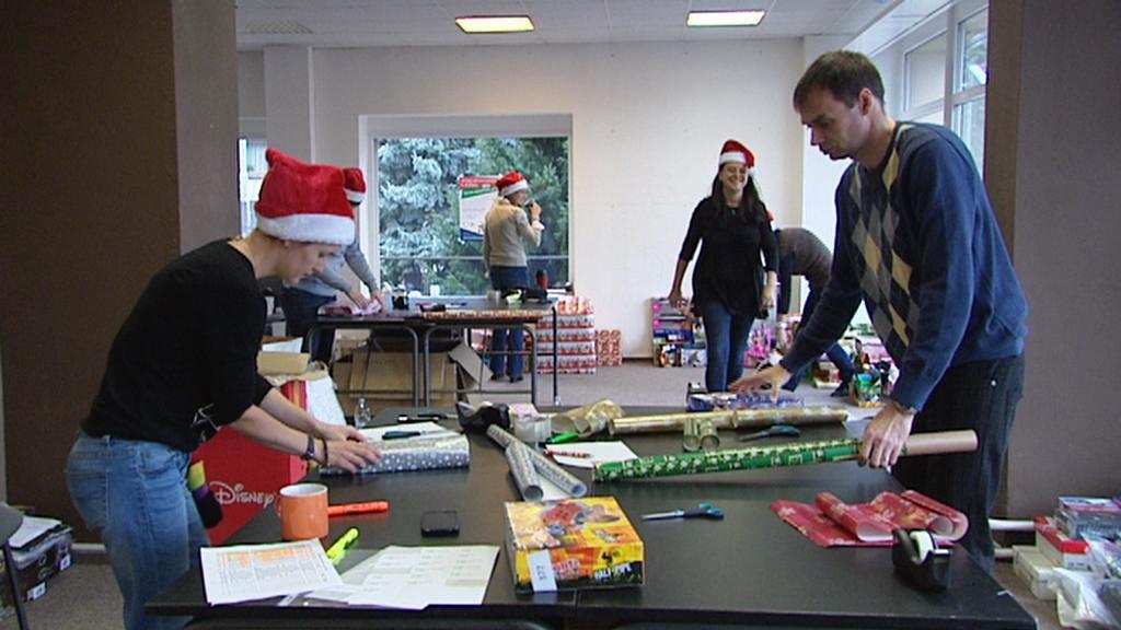 Dobrovolníci balí dárky pro děti z domovů